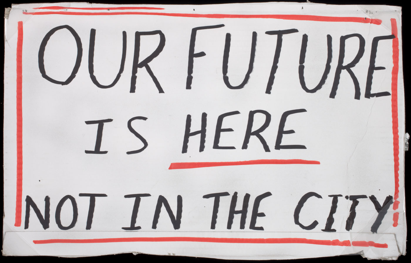 A placard made from a cut out of a cardboard box. There is black handwritten text against a white background on the front surface that reads 'OUR FUTURE / IS HERE / NOT IN THE CITY'. The text is surrounded by a drawn on red border and the word 'HERE' is also underlined with a red line. There is a yellow sticker on the back of the placard with the printed words 'BOURKE FURNITURE ONE / ...'.