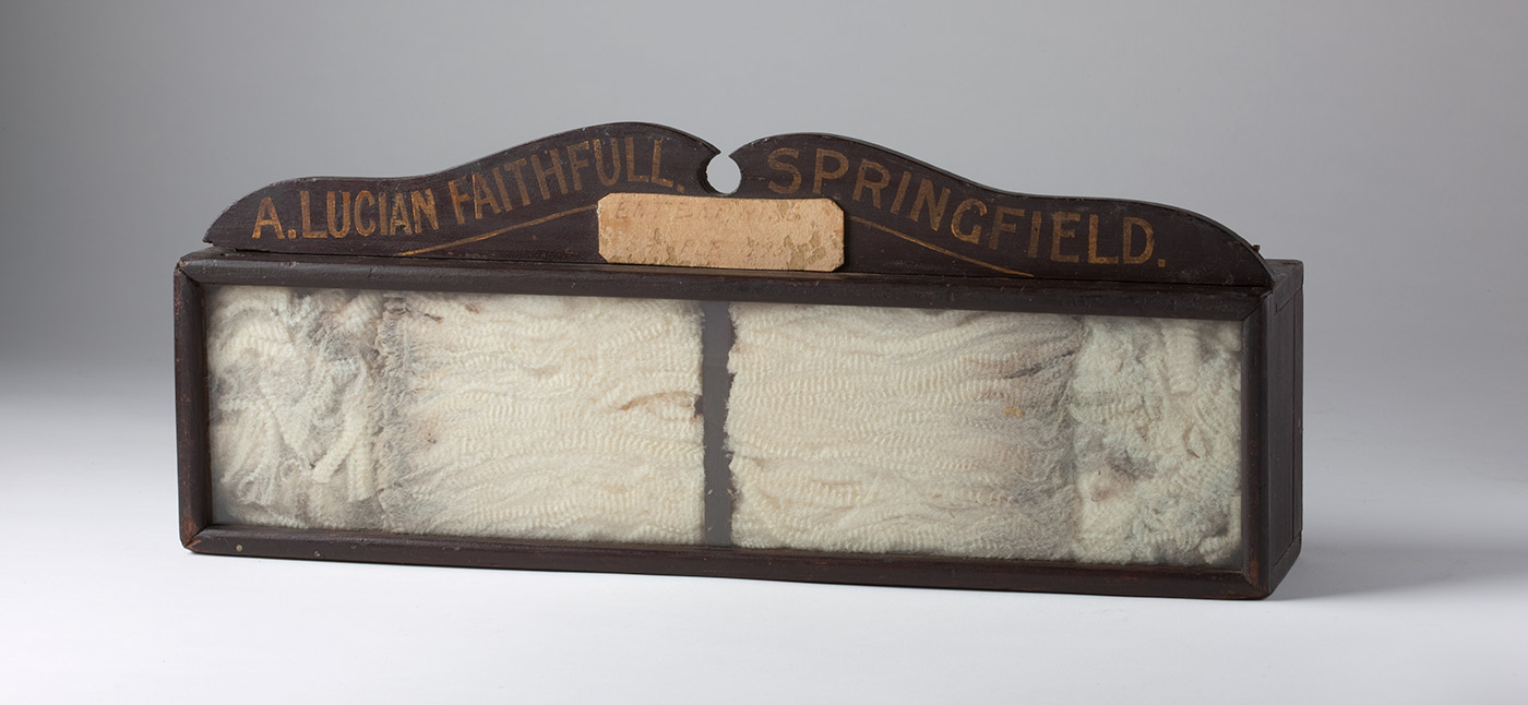 Glass-fronted wooden box, displaying a wool sample. Painted on a wooden banner at the top of the box: