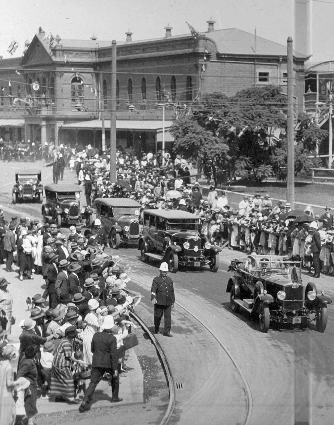 A black and white image showing five cars in a procession travelling past the South Brisbane Railway Station. Crowds line the streets with uniformed police officers patrolling. - click to view larger image