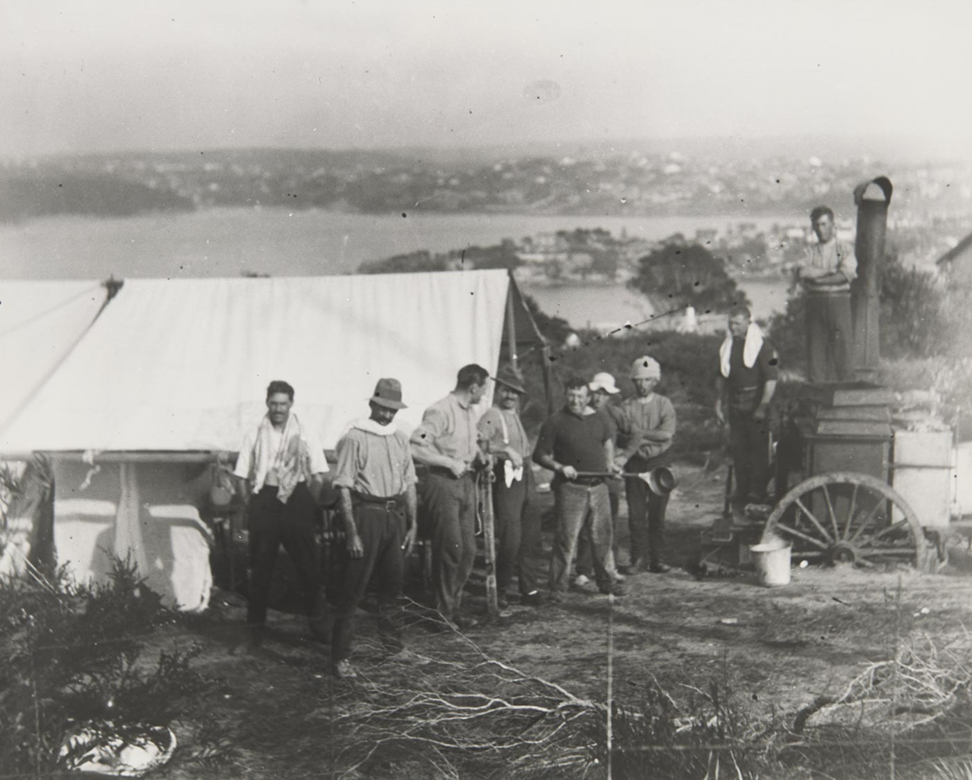 A black and white photograph of nine men standing outside a tent and next to a portable boiler. Some of the men have towels aroudn their necks and one is holding a long handled saucepan. Suburbs are visible on the headlands in the distance. - click to view larger image