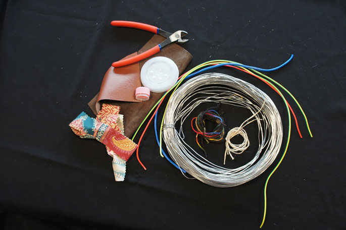 A range of materials including electrical wire, fencing wire, wire cutters, twine, wool and fabric scraps.