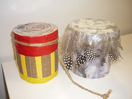 Two decorated drums. One is decorated with cardboard and red and yellow tape, the other is decorated with string and feathers.