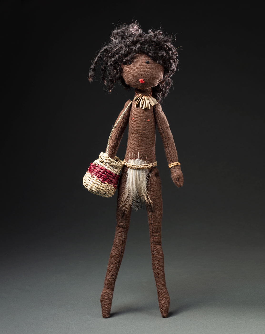A soft sculpture based on a female ancestor creator spirit Ngyardi, she is wearing a belt with feathers, has black wool hair and hand stitched black eyes and red lips. She is wearing a fibre bangle a necklace with leaves. She has a fibre work woven basket with her. - click to view larger image