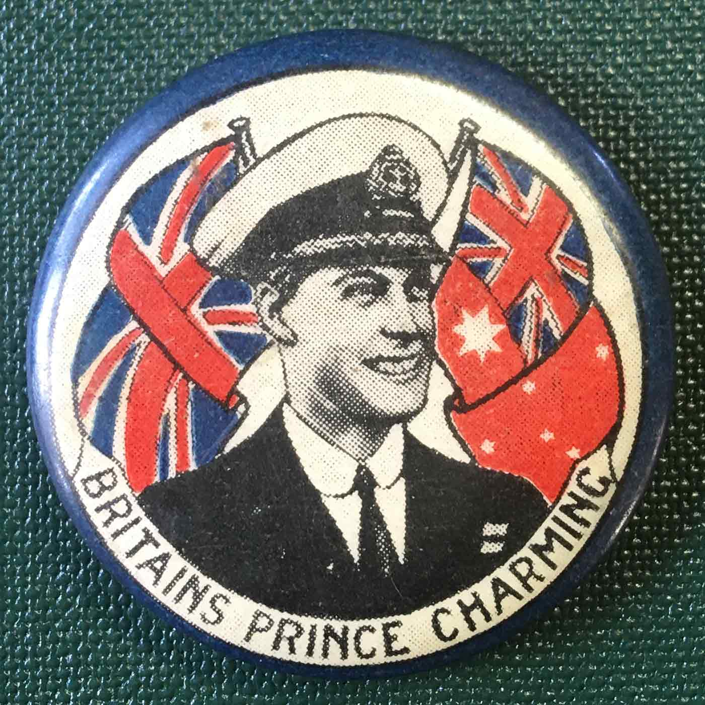 Colour photograph of a badge with an illustration of Prince Edward smiling in front of the British flag. There is a label with the text: BRITAIN'S PRINCE CHARMING. - click to view larger image