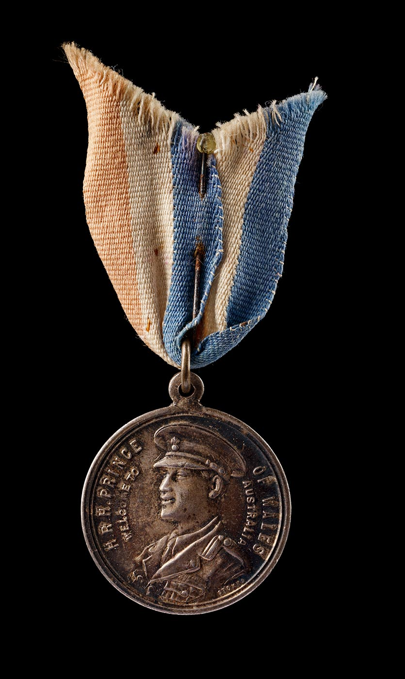 A silver coloured tarnished medallion with a protruding section at the top through which is a metal loop and a piece of faded red, white and blue ribbon held together by a rusted pin with a small glass top. The obverse of the medallion features a profile image of a man in a military cap and suit with the inscription 'H.R.H PRINCE OF WALES / WELCOME TO AUSTRALIA'. The reverse features a wreath within which is the inscription 'TO COMMEMORATE / THE VISIT OF / H.R.H. PRINCE OF WALES / TO AUSTRALIA / 1920'. - click to view larger image