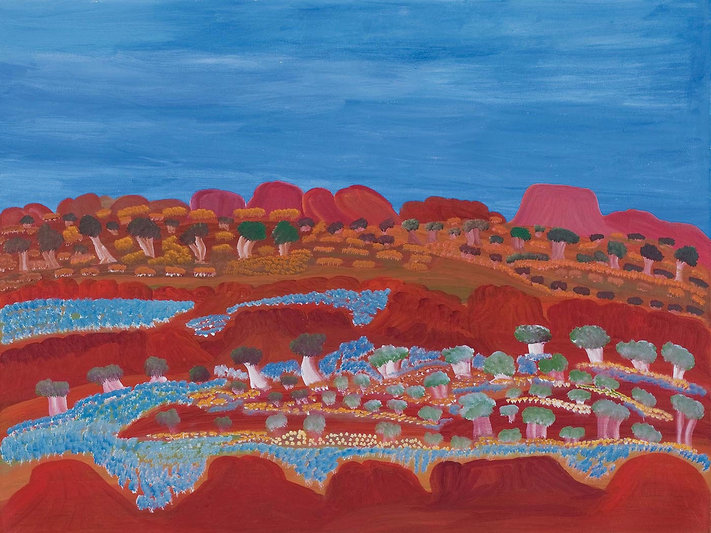 A painting on canvas with a range of orange-red rock formations lying low against a blue sky backdrop. In front of the formations are green and light brown trees and yellow-brown grass-like foliage. In the foreground are two horizontal rows of orange-red rock formations creating a valley-like appearance. The valley and some of the rock formations are covered in expanses of flowers in blue, yellow and cream as well as trees in green and beige-white.