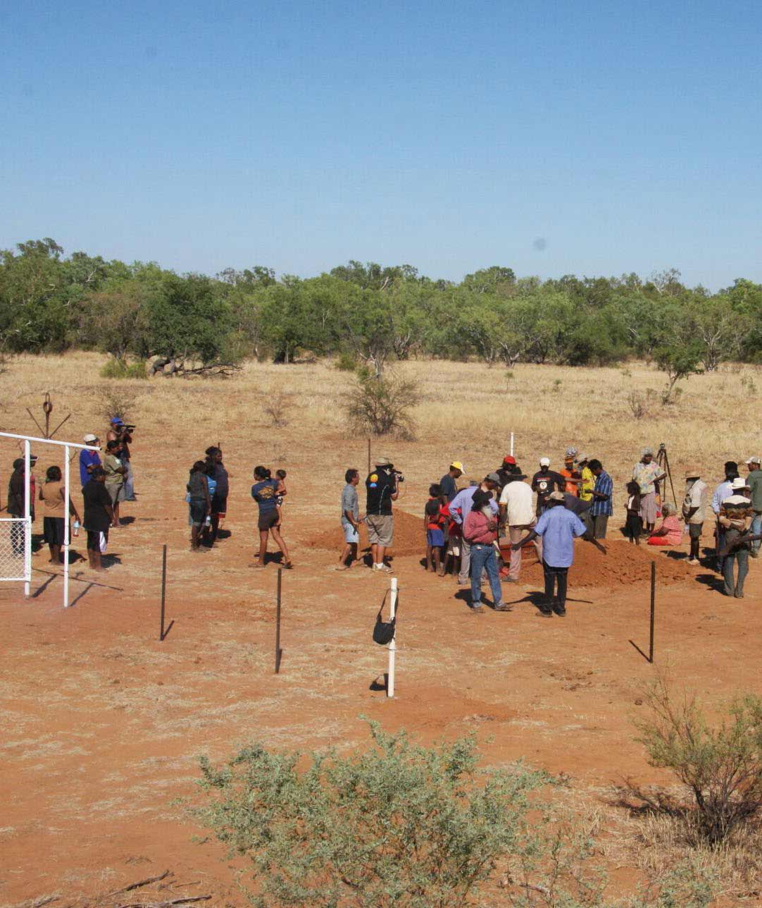 Photo of a group of people observing and filming a burial ritual.