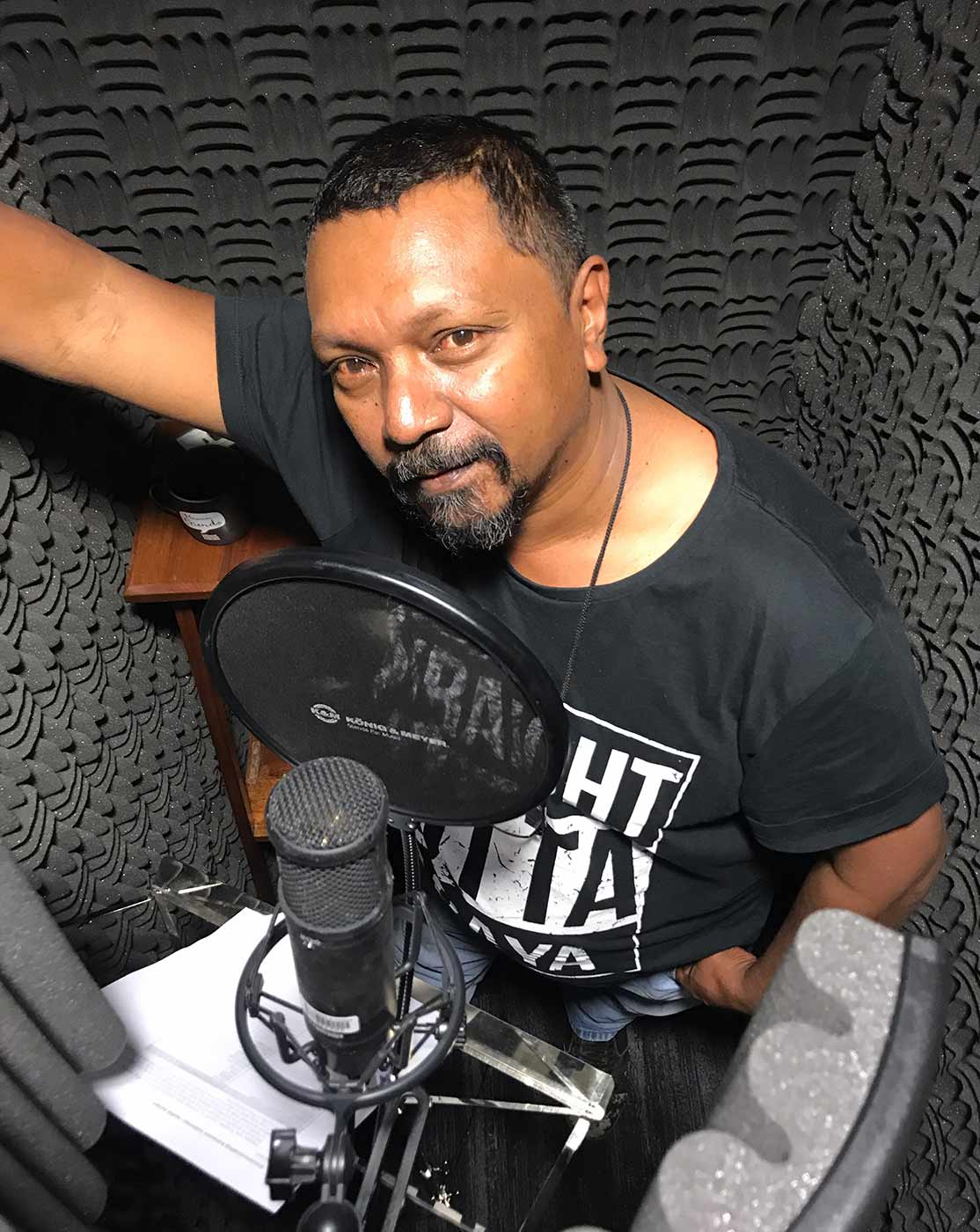 Colour photograph of a man in a soundproof booth of a recording studio. He is speaking into a microphone. - click to view larger image