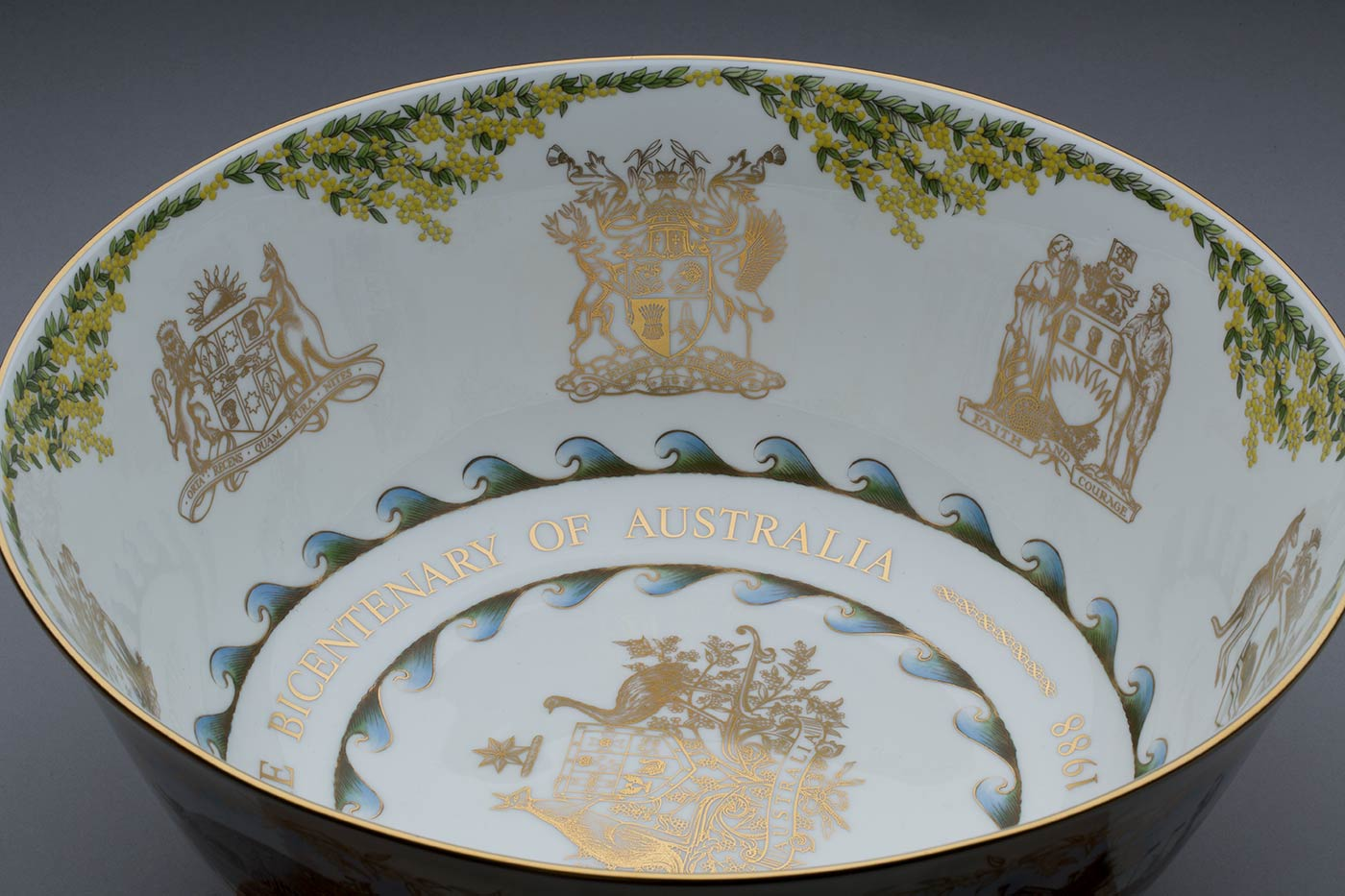 Commemorative hand-painted bone china bowl. The bowl is made of fine bone china, which is composed of feldspathic rock, English china clay, and about fifty percent calcined animal bone. The inside of the bowl features a border of wattle and the coat of arms of each State, Territory, and the Commonwealth of Australia, in 24 carat gold. 'To Commemorate the Bicentenary of Australia 1788-1988' encircle the inside base. A wave motif surrounds the words, symbolising Australia's ties with Britain and countries around the world. Hand-painted scenes of the national capital decorate the outside of the bowl. From left to right they are the Old Parliament House; the Australian War Memorial; the High Court; the Carillon; Duntroon House; Blundell's Cottage; St John's Church; Black Mountain Tower; the Australian Academy of Science; the Captain Cook Memorial Water Jet; Government House; and the Ethos Statue in Civic Square. - click to view larger image