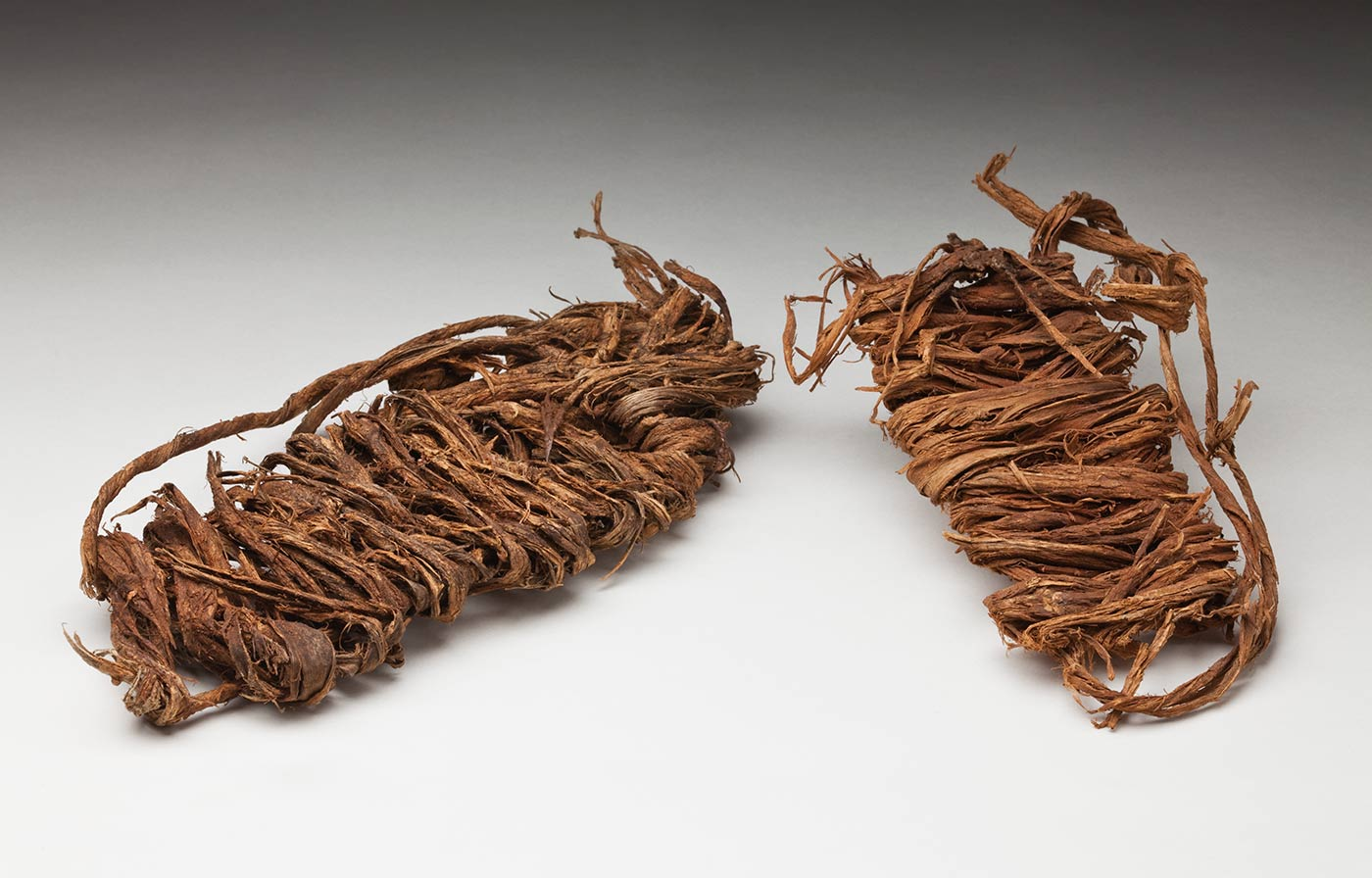 A pair of undyed bark sandals made from thick bark string. The pair have a piece of jute string tied around them, keeping them together. - click to view larger image