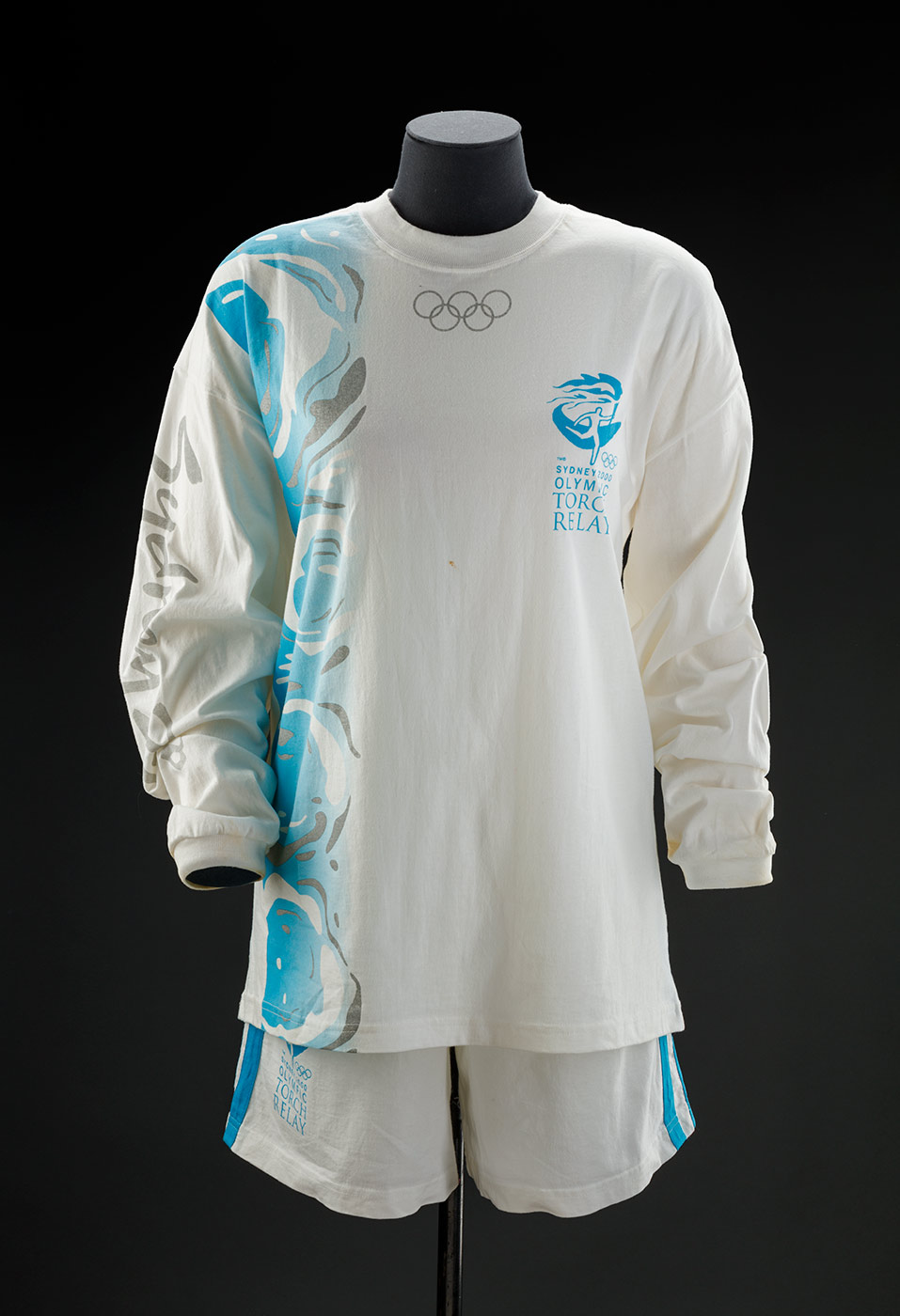 A white long sleeve stretch cotton shirt with a logo of a person running and the text 'SYDNEY 2000 / OLYMPIC / TORCH / RELAY' in light blue. There is a rectangular design running down the proper right front and back, with white and grey swirls on it. The Olympic rings in grey are printed below the neckline, and the word 'Sydney' is printed in grey on the right arm. The neck and cuffs have white ribbing. - click to view larger image