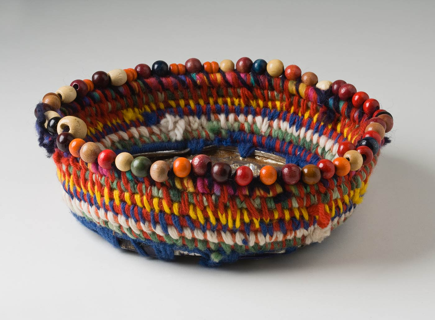 A shallow circular coiled multicoloured yarn and plant fibre basket with metal base and bead trim. The base is made of a 'Fray Bento / Steak and Kidney Pie' tin that has been unevenly flattened and shows blackening from heat. This is attached to the yarn and fibre section by yarn threaded through holes punched in the tin. The yarn is in rainbow colours with red and blue being the most dominant. At the top edge is a circle of red, orange, beige, brown, navy and green round wood beads with a few cylinder beads included. - click to view larger image