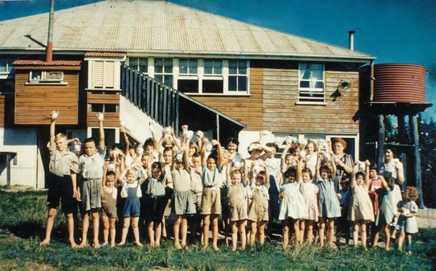 Colour photograph showing a large group of children, with their hands in the air, in front of a raised homestead and water tank.  - click to view larger image