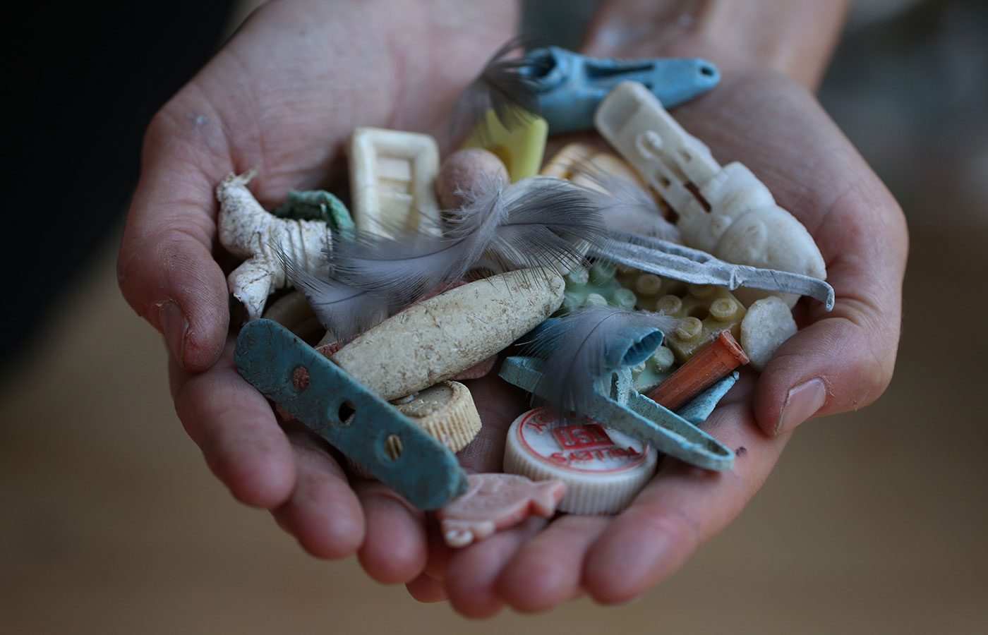 A pair of hands holding a variety of plastic articles retrieved from the ocean.