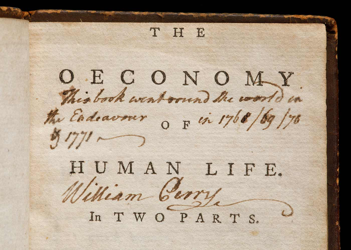Close up view of a book featuring the title 'The Oeconomy of Human Life' on the title page. The title-page has the text [handwritten by William Perry] in black ink that reads 'This book went round the World on the Endeavour in 1768 / 69 / 70 & 1771', with Perry's signature underneath. - click to view larger image
