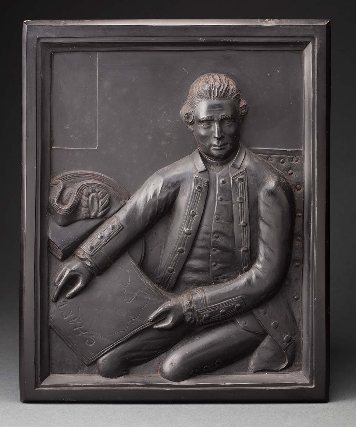 Portrait plaque carved from kerosene shale, depicting Captain Cook in relief, seated ( facing the viewer) and holding a chart. - click to view larger image
