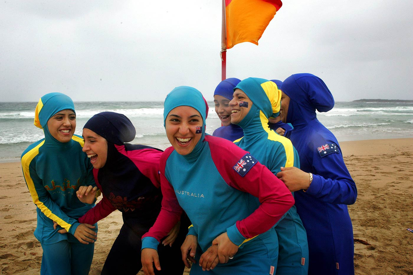 A group of young women of middle-eastern appearance laughing and embracing each other. They are wearing colourful beach wear that has been designed to include the burqa.