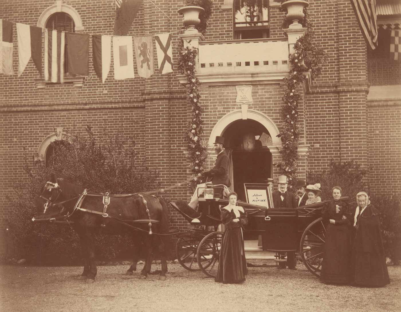Sepia coloured photograph showing a landau carriage pulled by a horse standing in front of the homestead entrance with the honeymoon couple being greeted by relatives.