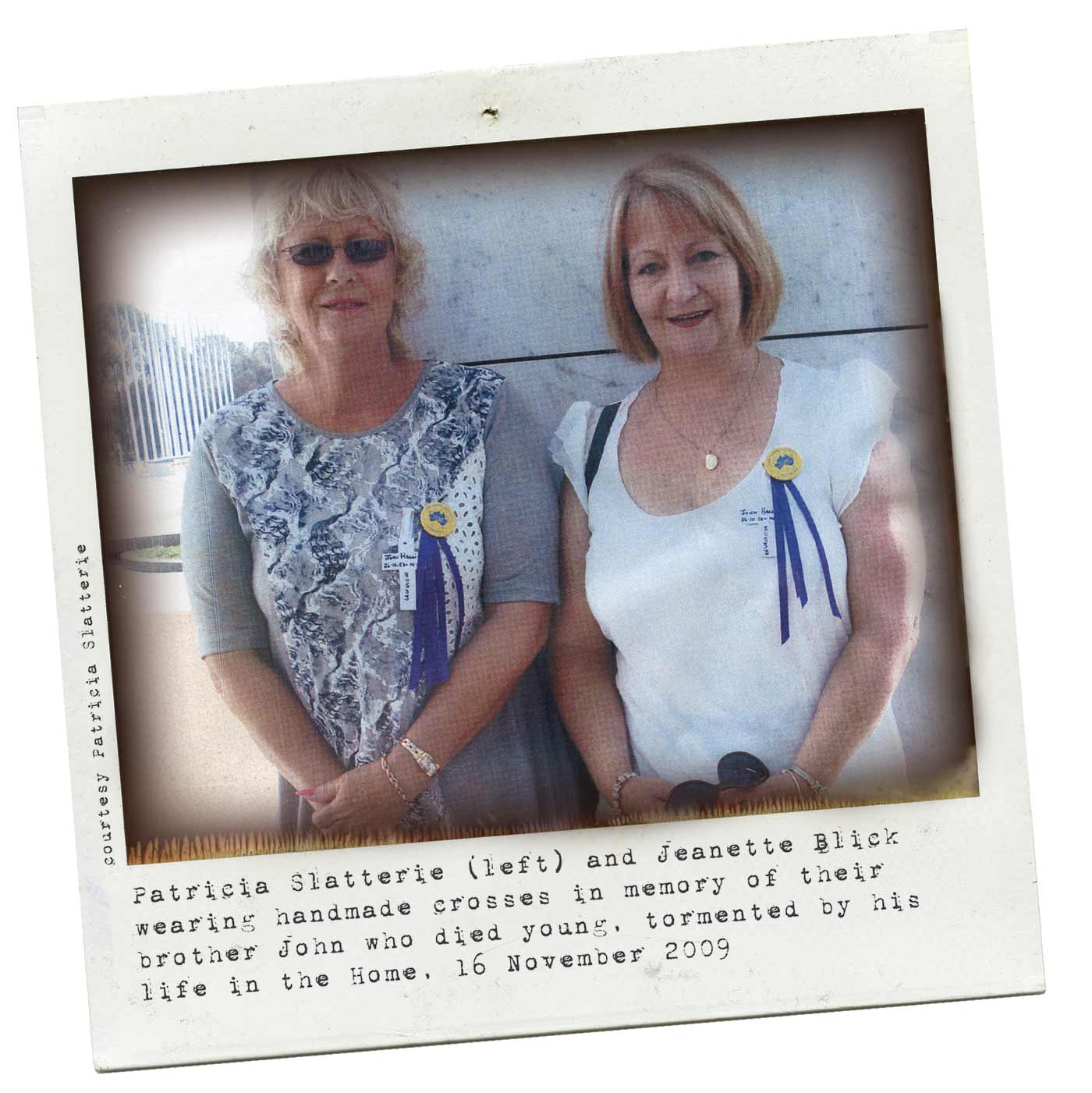 A colour Polaroid image of two women wearing badges and blue ribbons pinned to their shirts. Typewritten text below reads 'Patricia Slatterie (left) and Jeanette Blick wearing handmade crosses in memory of their brother John who died young, tormented by his life in the Home, 16 November 2009.' 'Courtesy Patricia Slatterie' is typed along the left side. - click to view larger image