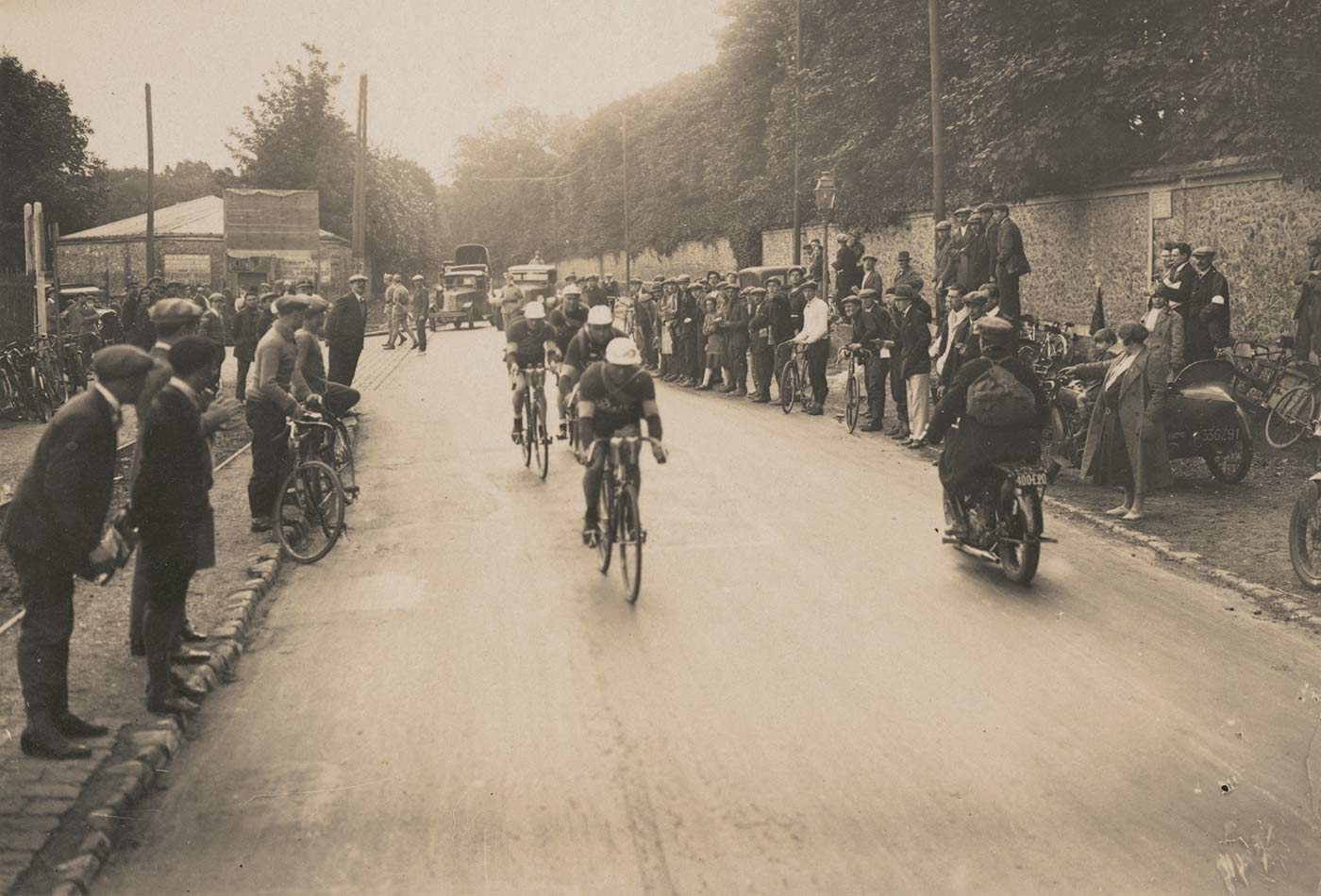 A black and white photo of Hubert Opperman leading a four-man team through a village during the Tour de France, 1928.  - click to view larger image