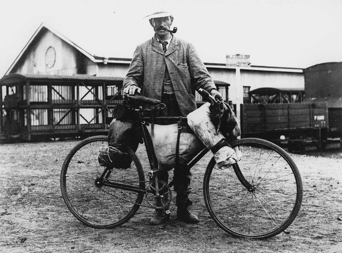 A black and white photograph of a man with a bicycle.  Handwritten text at the bottom of the photo reads: 'A shearer, moving camp.' - click to view larger image