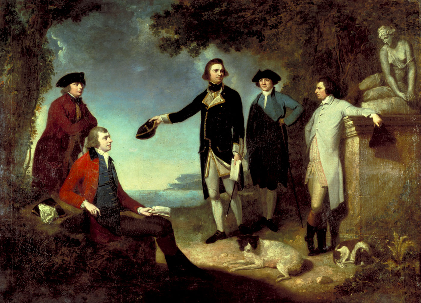 Oil painting showing five men in an Arcadian landscape, with a marble statue of a seated woman at right and two dogs lying at the men's feet. The man at centre gestures towards a bay.