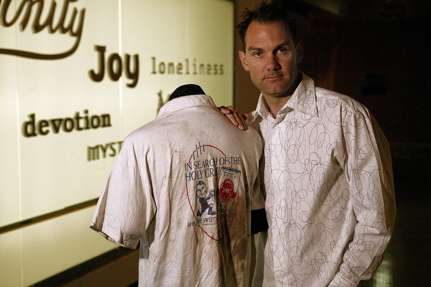Man standing with his hand resting on a mannequin displaying a white t-shirt with an image and text on the back - click to view larger image
