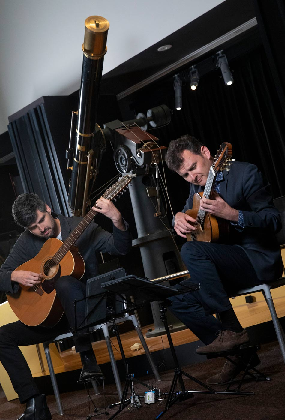 Slava and Leonard Grigoryan play guitars in front of a large telescope. - click to view larger image