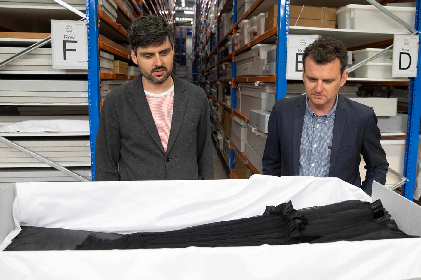 Slava and Leonard Grigoryan inspect a black lace dress displayed in a conservation box.