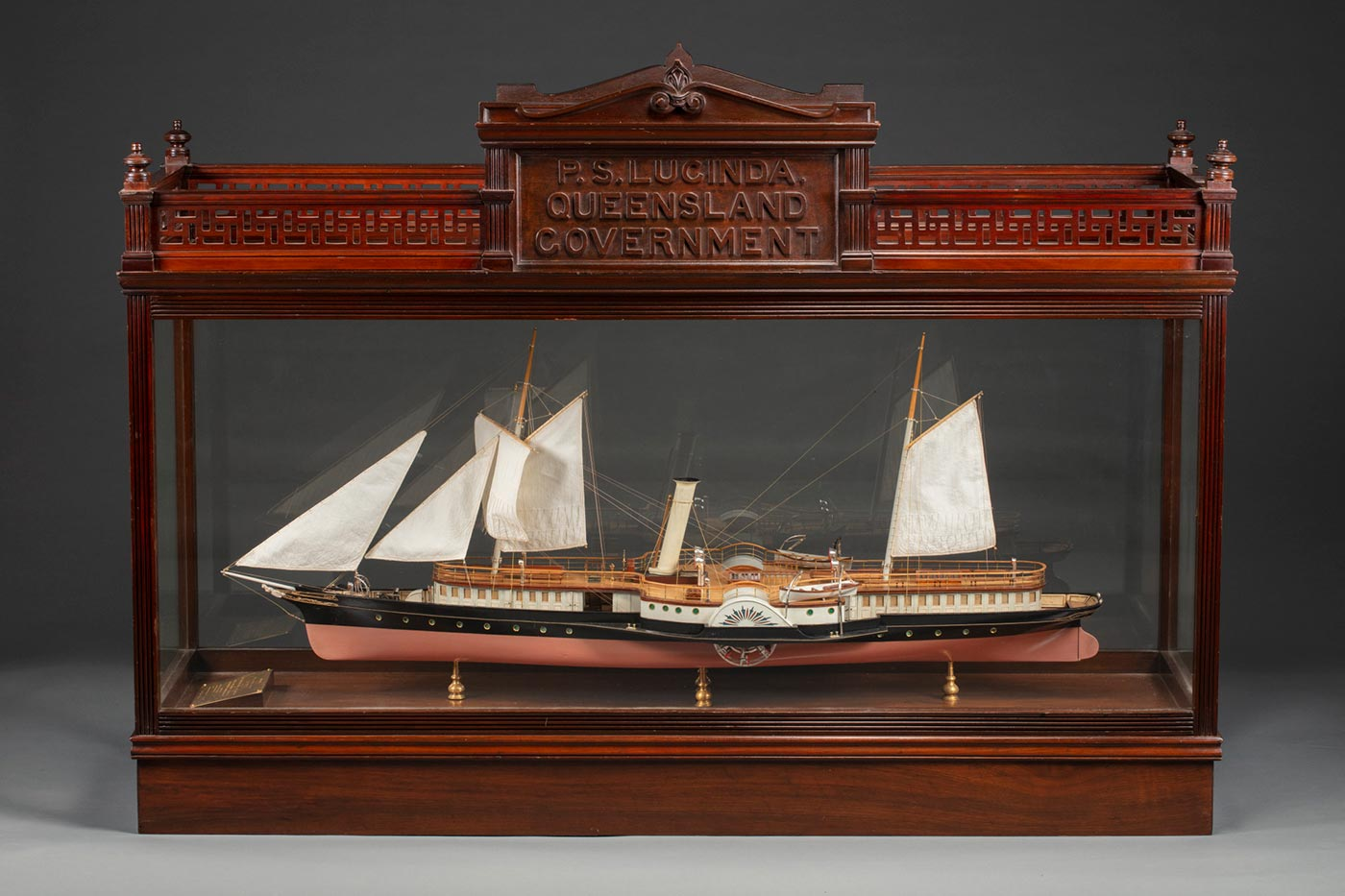 A model of a ship in a wood and glass case, the ship has five raised sails, water wheels on either side, painted in black and brown with details in blue and red, held on four gold coloured stands, and a gold plaque at one end. Th case is in good condition and has an engraved panel with the text: