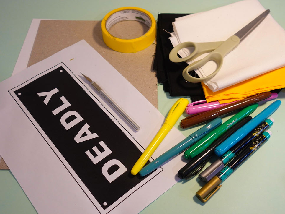Craft activity featuring a range of materials including tape, scissors, paper, colouring pens and a stencil of the word 'DEADLY'.