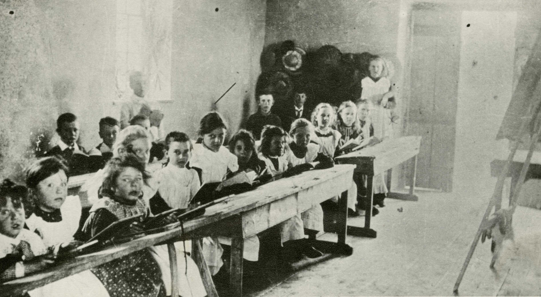 Black and white photograph of school chidren sitting at desks in a school room.