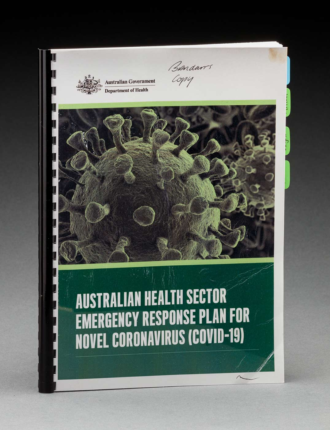 An A4-sized booklet with plastic binding features a front cover with the logo for the Australian Government Department of Health and the text: 'AUSTRALIAN HEALTH SECTOR / EMERGENCY RESPONSE PLAN FOR NOVEL CORONAVIRUS (COVID-19)'. Handwritten at the top is the text: 'Brendan's copy'. - click to view larger image