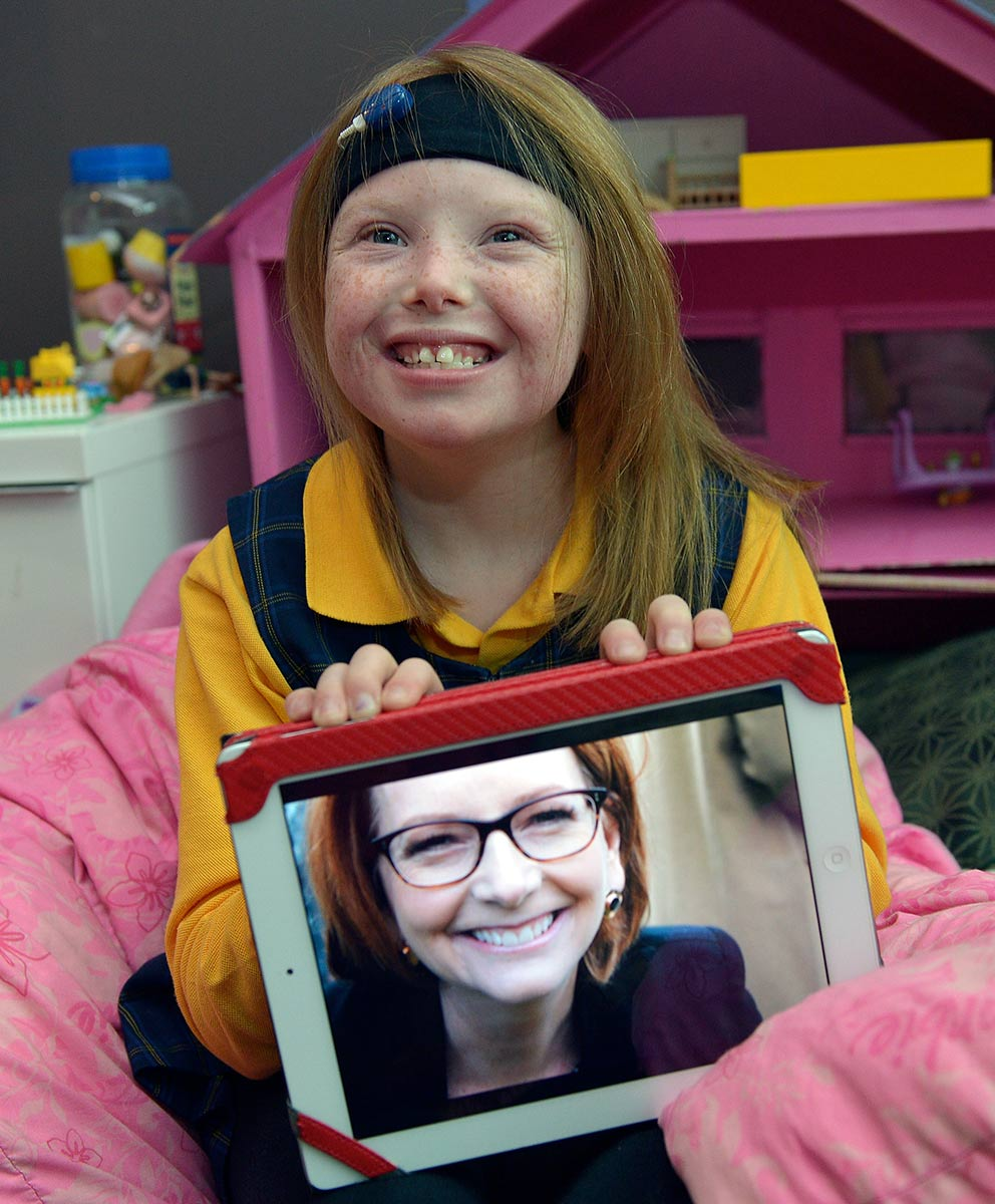 A young girl with a big smile sits on a pink beanbag displaying a photograph of Julia Gillard. - click to view larger image