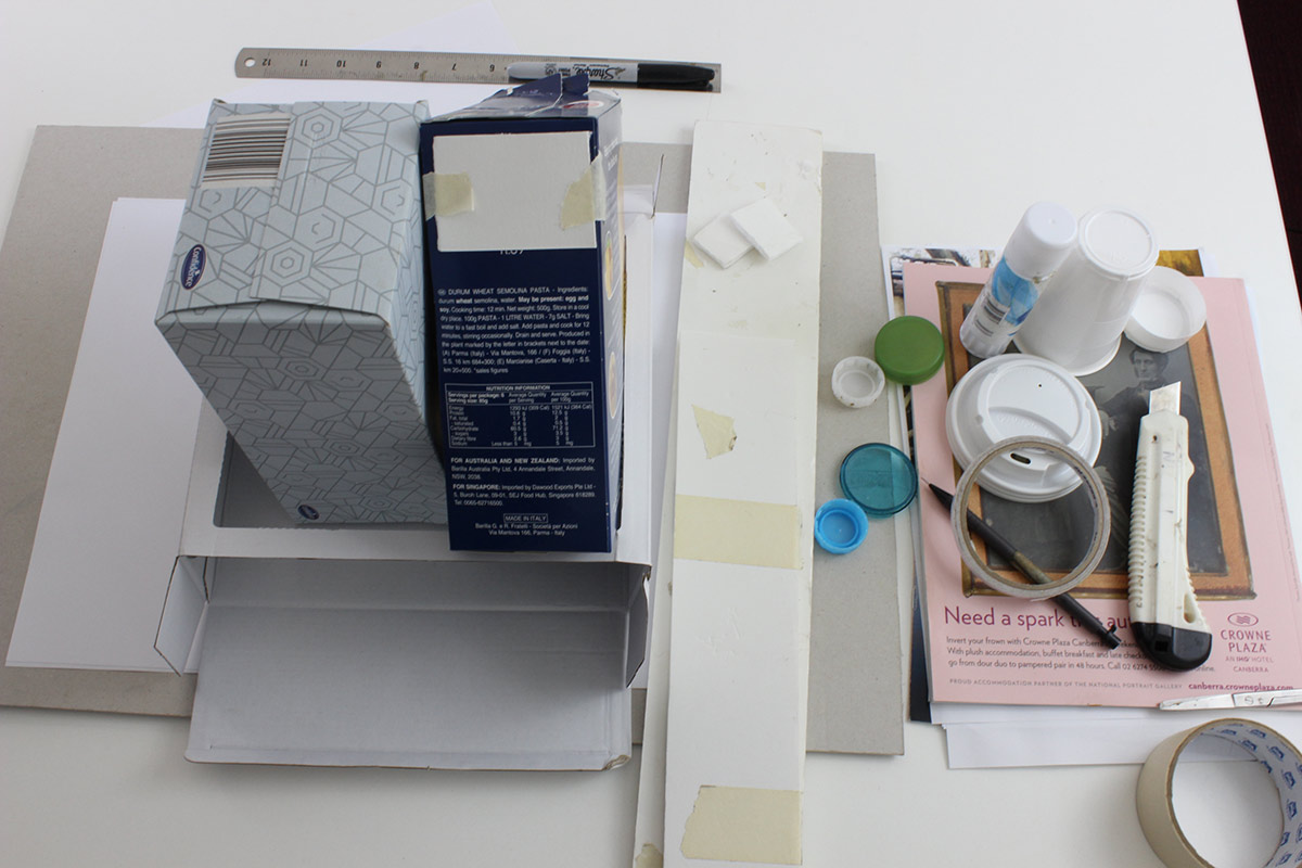 Various materials for a craft project including cardboard boxes, plastic lids and cups, glue, tape, ruler, pen, etc.