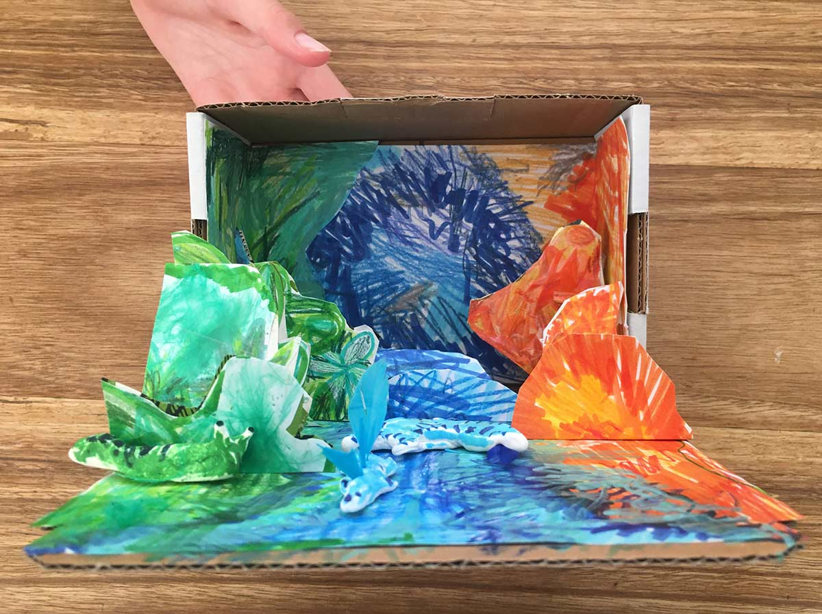 A cardboard box revealing a nature-themed interior of various cut out shapes coloured with shades of green, blue and orange texta. - click to view larger image
