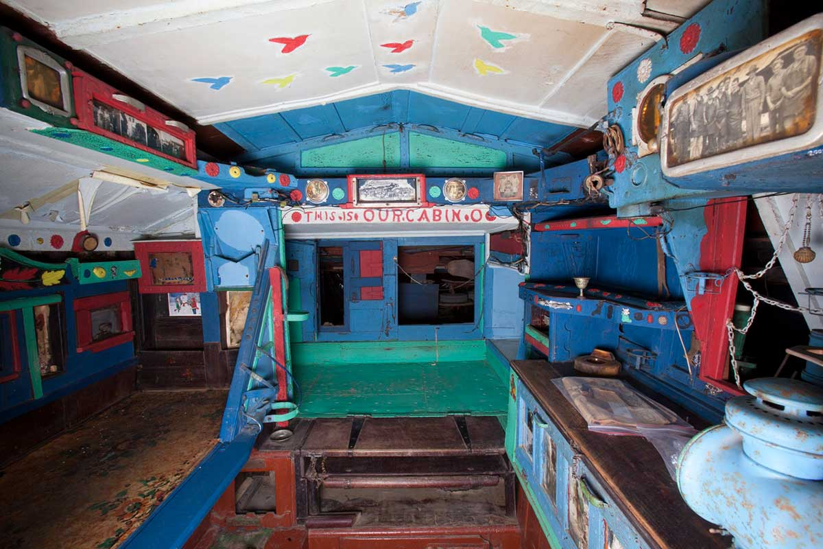 A colour photograph of the interior cabin section of the Saw Doctor's wagon. A partially visible sign reads 'THIS IS OUR CABIN'. - click to view larger image