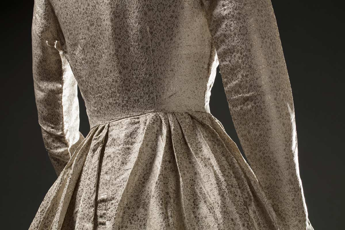 Cropped image of a cream-coloured synthetic brocade dress showing the back of the waistline area. - click to view larger image