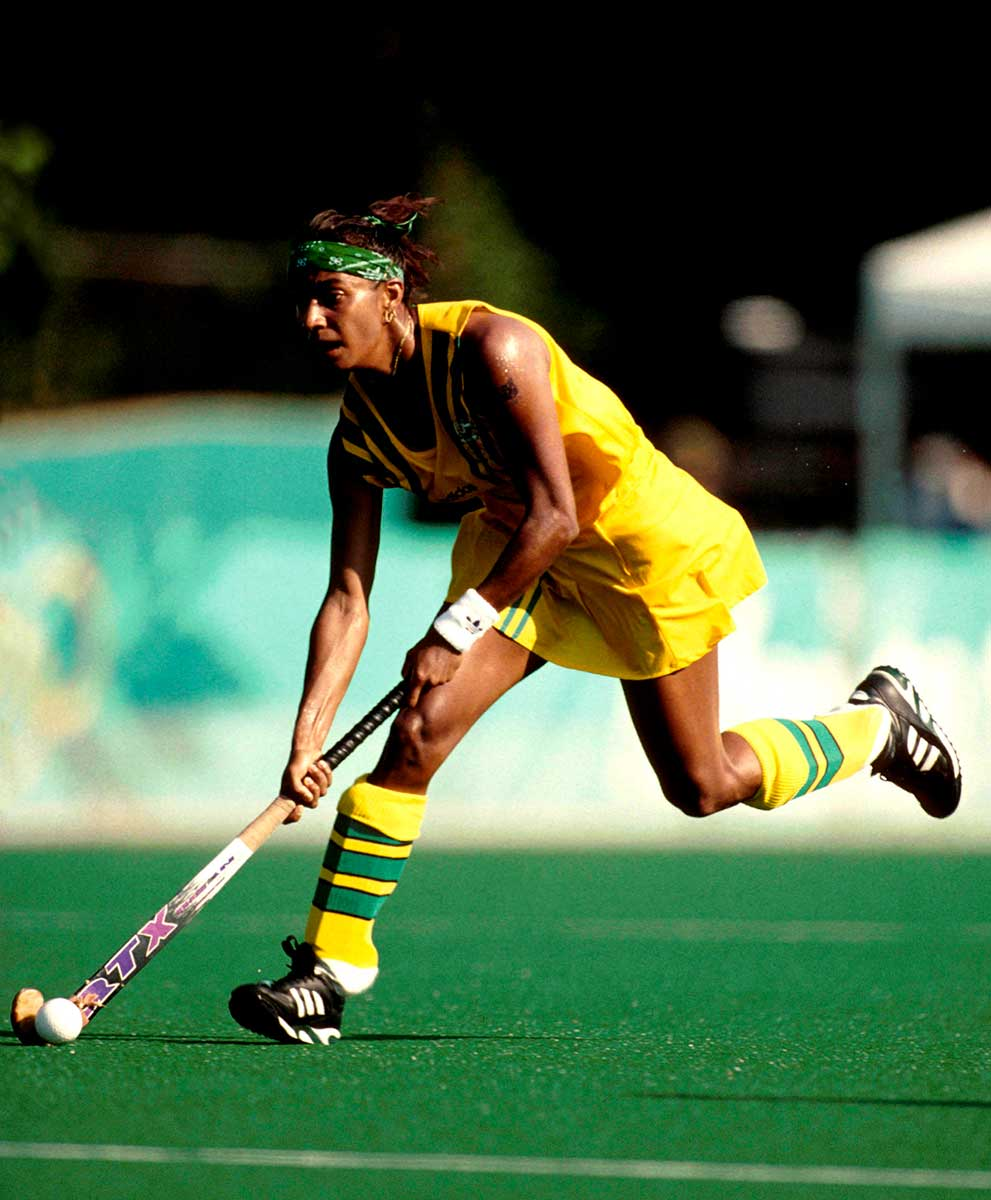 A woman in a green and yellow uniform running with a hockey stick across a field. - click to view larger image