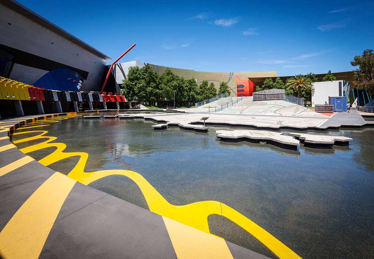 Outdoor recreational space featuring a large water feature with a concrete sculpture in the shape of a map and continent. - click to view larger image