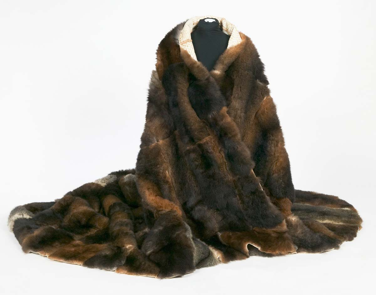 Animal skin pelts stitched together to form a cloak which is displayed on a mannequin. - click to view larger image