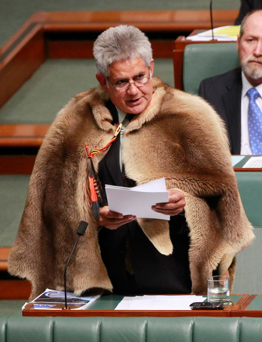 Member of Parliament Ken Wyatt wearing an animal pelt draped over his suit, addresses Parliament. - click to view larger image
