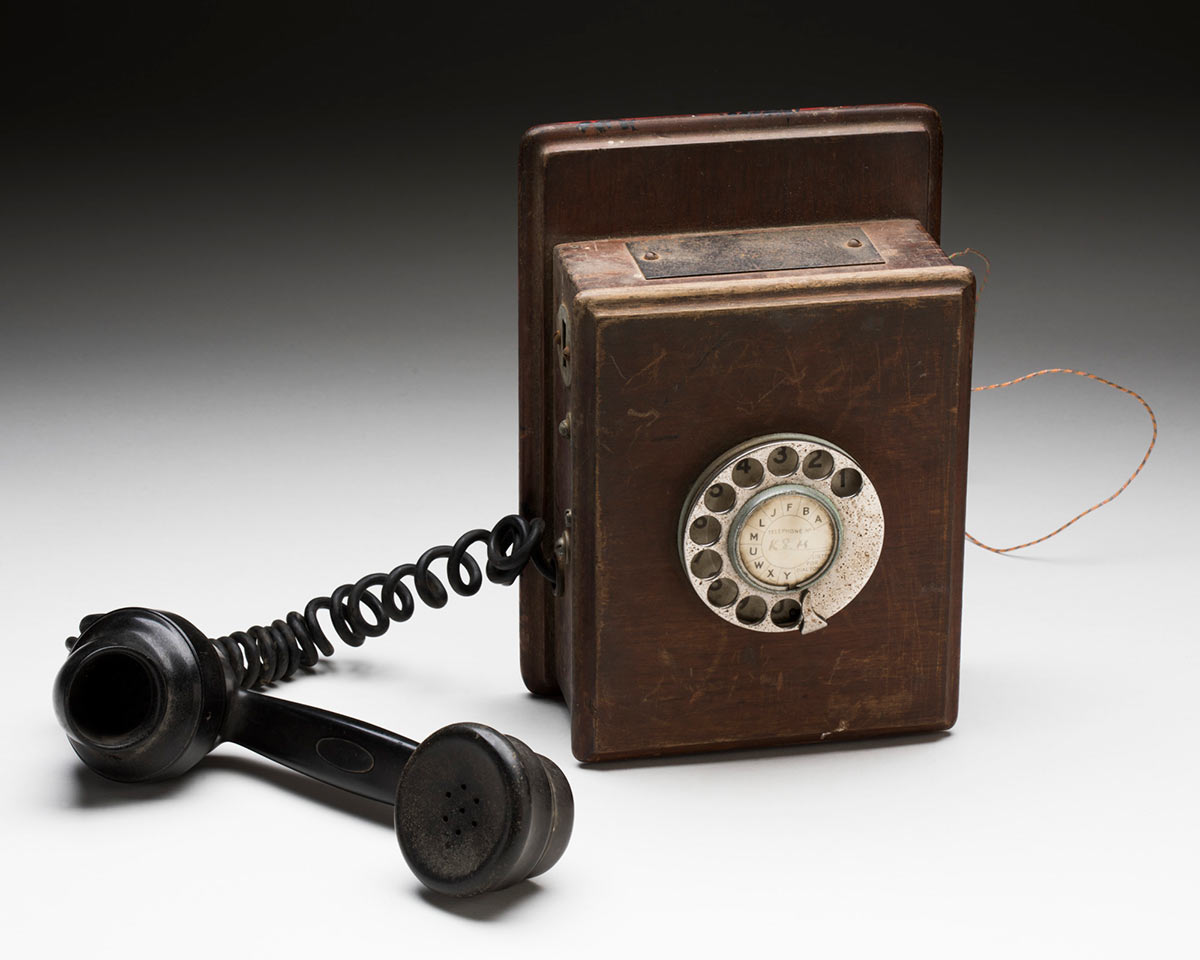 Brown wooden wall telephone with a black plastic handset, a wooden peg and a silver metal dial with numbers and letters. The centre of the dial has