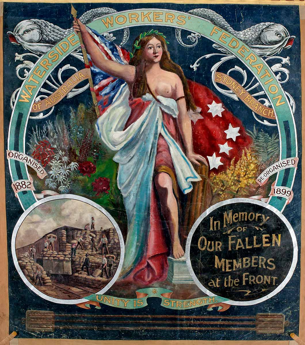 Banner with a central image of a robed woman holding the red ensign. She stands surrounded by Australian wildflowers. A small circular inset at the bottom left of the banner depicts shows men stacking and carrying sacks. An inset on the right says 'In Memory of Our Fallen Members at the Front' . 'Waterside Workers Federation' heads the banner and the words 'Unity is Strength' appear at the bottom. - click to view larger image