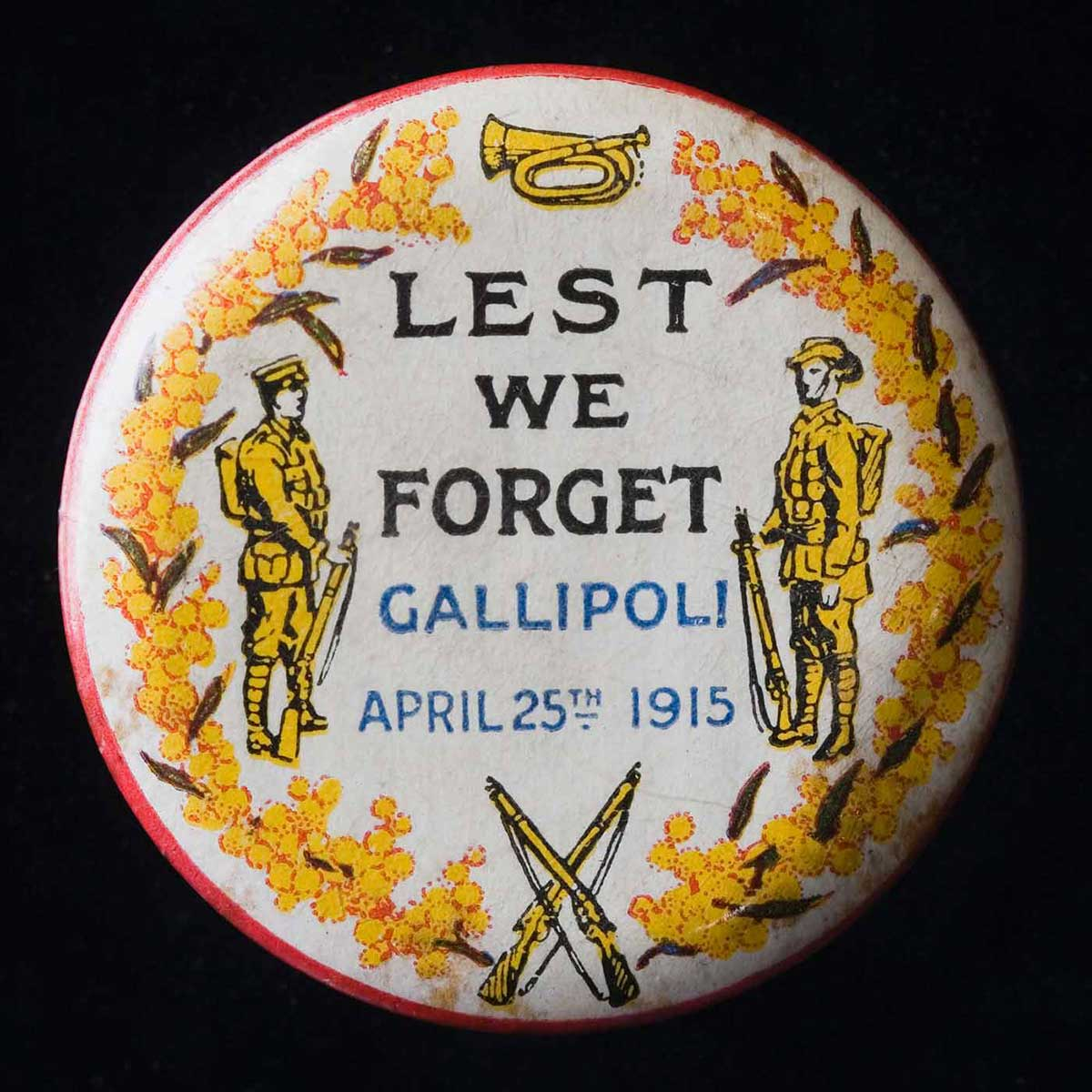 Circular badge bordered by a wreath of wattles, with a bugle at the top and two crossed rifles at the bottom. Two soldiers stand at ease either side of the central image, beside the text 'Lest We Forget, Gallipoli, April 25th 1915'. - click to view larger image