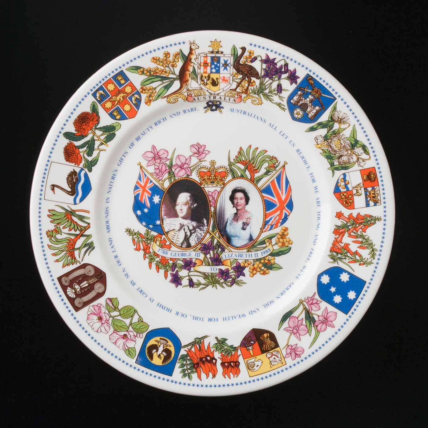 A coloured photograph of a plate which with the Australian coat of arms, state heraldry and floral emblems around its border. At the centre of the plate there are portraits of King George III and Queen Elizabeth II, surrounded by Australian flowers, the Union Jack and Australian flag. Some of the words from the national anthem are printed around the plate: 'Australians all let us rejoice, for we are young and free, we've golden soil and wealth for toil, our home is girt by sea, our land abounds in nature's gifts of beauty rich and rare ...'  - click to view larger image