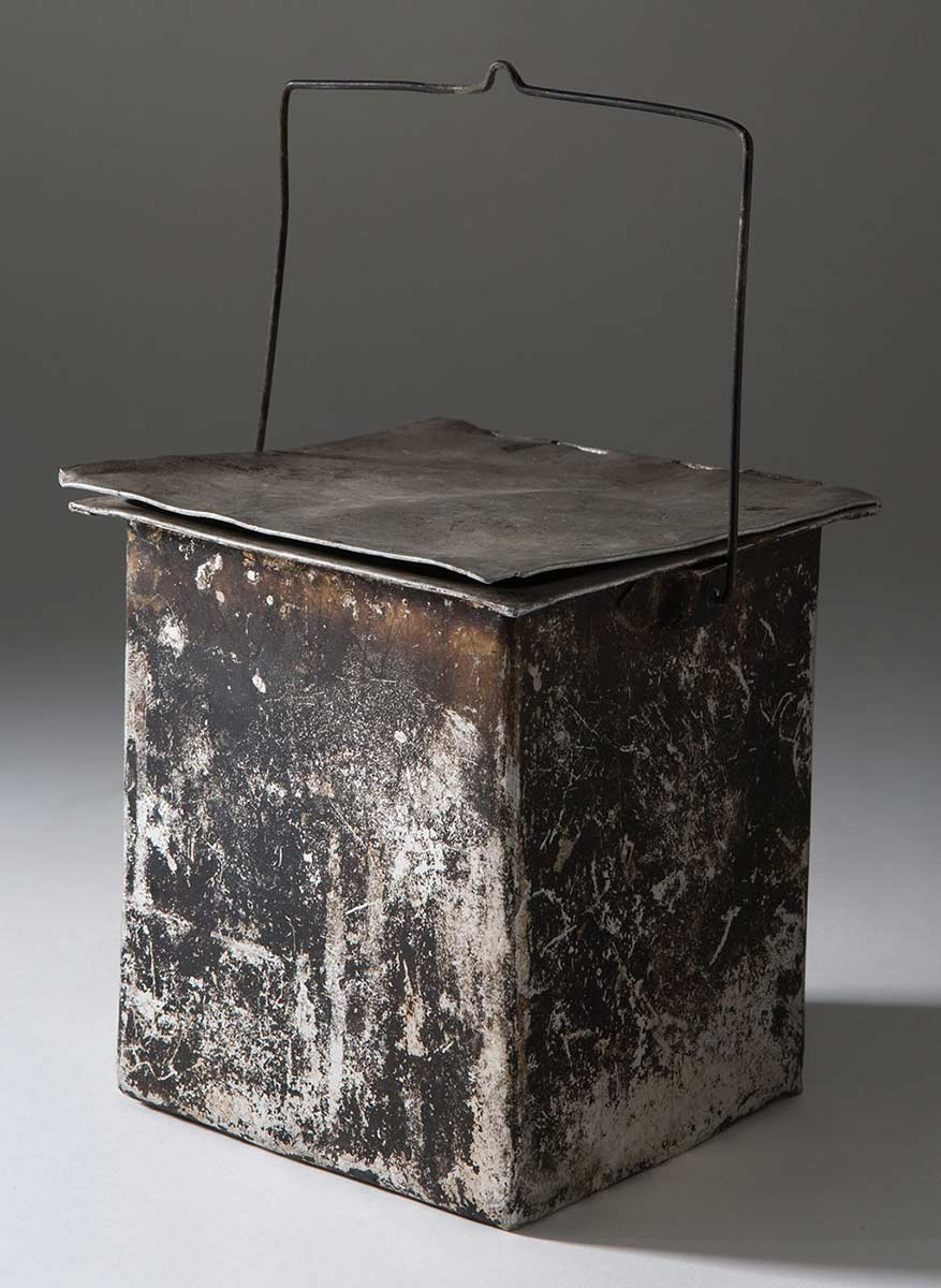 A rectangular-shaped metal vessel with a lid and wire handle, which bears marks of being used in a fire. - click to view larger image