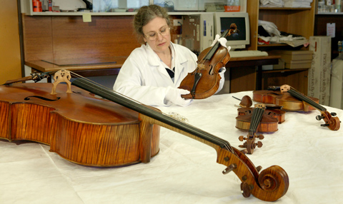 A woman wearing a white laboratory coat and gloves holds a wooden stringed instrument while sitting at a table. Three other wooden stringed instruments lie on the table.