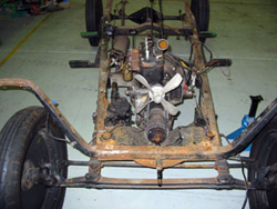 Rusting car frame and engine.