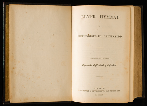 A Welsh hymnal, open. The left page is blank. The right page is headed 'LLYFR HYMNAU'